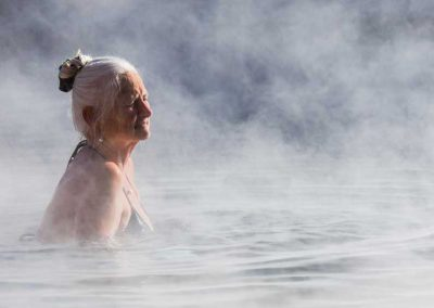 Women enjoying the warm pool with steaming rising off of water.
