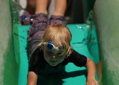 Little boy enjoying slide.