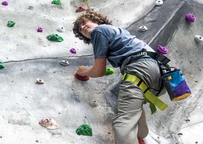 Teenager climbing on indoor rock wall.