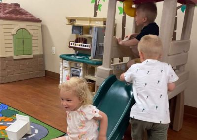 Kids playing inside of daycare center.