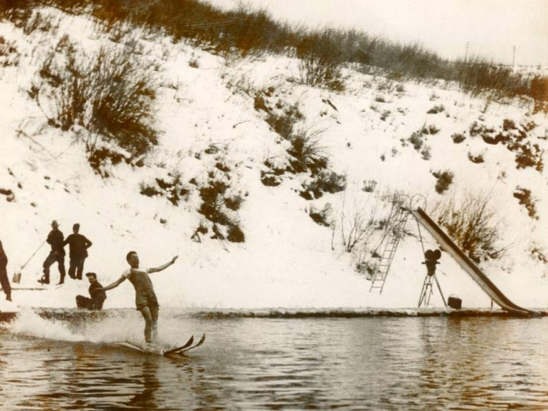 Man skiing off of snowy hillside into a warm pool of water at the Old Town Hot Springs in 1940.